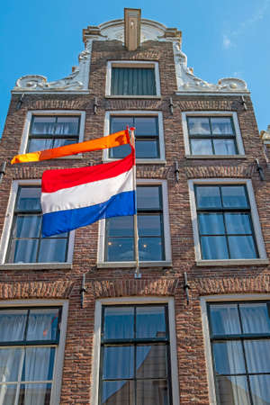 Old medieval townhouse with the national dutch flag and orange banner in Amsterdam the Netherlands