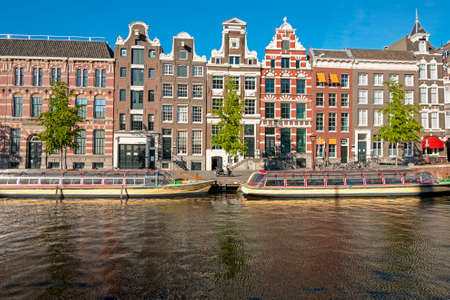 Medieval houses and cruise boats in the city center from Amsterdam in the Netherlands