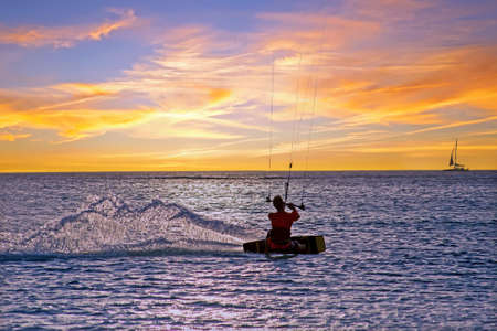 Kite surfing at Palm Beach on Aruba island in the Caribbean Sea at sunset