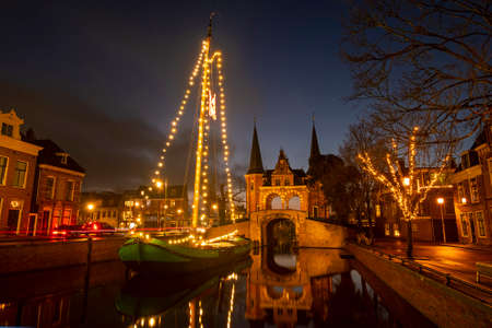 Decorated traditional sailing ship at the Water Gate in Sneek in the Netherlands in christmas time at night