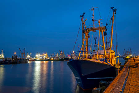 Fishing boats in the harbor from Lauwersoog in the Netherlands at night
