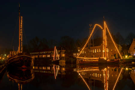 Decorated traditional boats in the harbor from Dokkum in the Netherlands at christmas at night 免版税图像