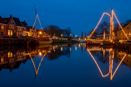 Decorated traditional boats in the harbor from Dokkum in the Netherlands at christmas at sunset