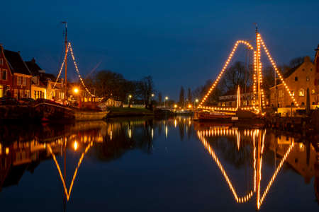 Traditional boats in the harbor from Dokkum in the Netherlands in christmas time at twilight