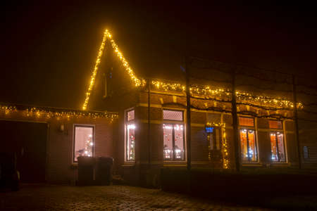 Traditional decorated dutch house in the countryside from the Netherlands with christmas at night
