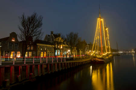 Decorated traditional sailing ship in the harbor from Harlingen in the Netherlands in christmastime at night