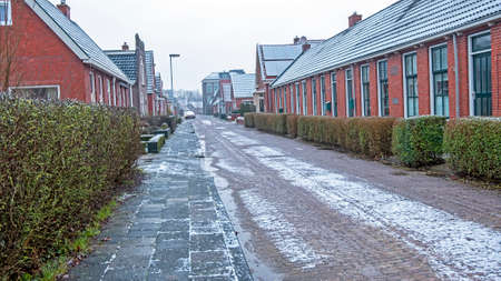 Traditional old snowy dutch street in winter in the Netherlands Фото со стока