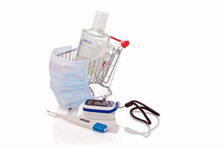 Desinfentant gel, thermometer, blood saturation meter and a medical mask in a shopping cart, concept