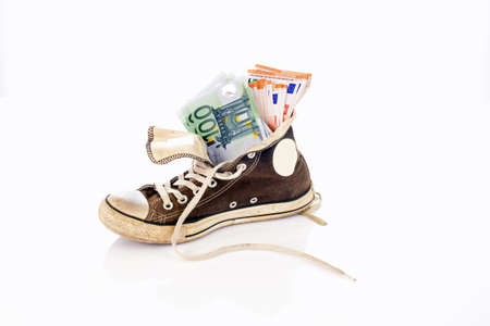 Euro banknotes in an old sneaker on a white background
