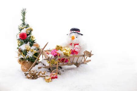 Christmas man in a wooden cart with presents at the christmas tree in the snow on a white background 免版税图像