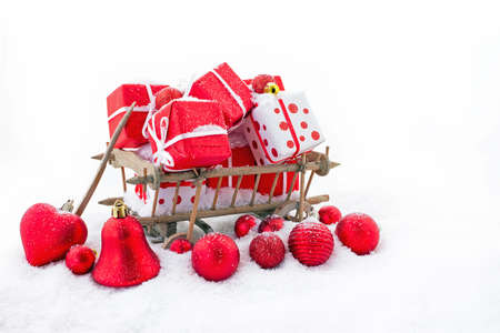 An old wooden cart full of christmas gifts in the snow
