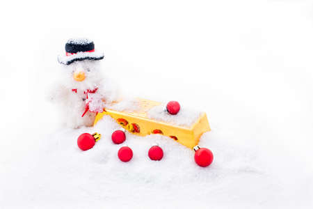 Christmas man with a gold bar and red christmas balls in the snow