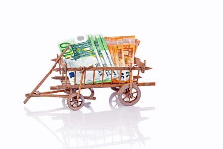 An old wooden cart full of money on a white background