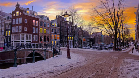 City scenic from a snowy Amsterdm in winter in the Netherlands at sunset