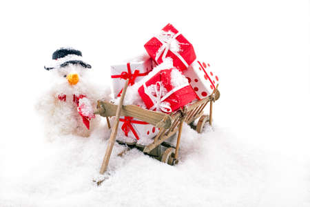 Christmas man with a wooden cart full of gifts in the snow 免版税图像