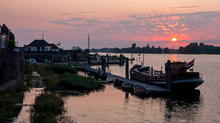 The harbor from Woudrichem at the river Merwede at sunset in the Netherlands 免版税图像
