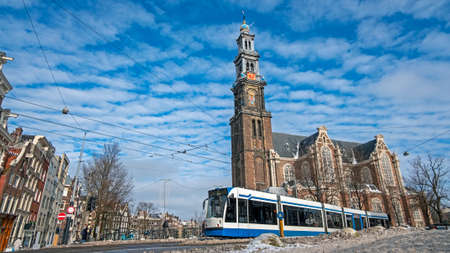 City scenic from a snowy Amsterdam in winter near the Westerkerk in the Netherlands