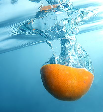 blured: Fresh orange jumping into water with a splash. Little motion blured.