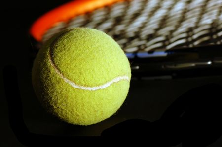 proffesional: Tennis equipment - ball and racket on black. Soft light, shallow depth of field.