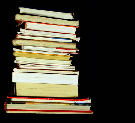 hardback: Books pile isolated on black with empty, editable space Stock Photo