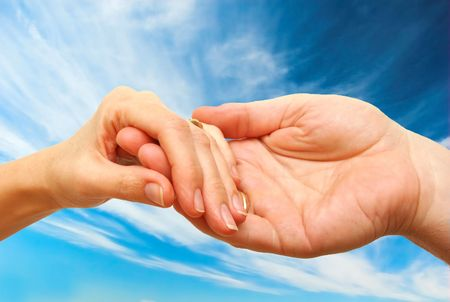 Two hands - woman and man touch each other in delicate, subtle way on sky background photo