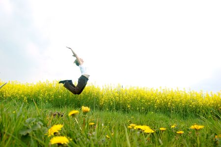 Happy young woman jumping on spring meadow Stock Photo - 1105588