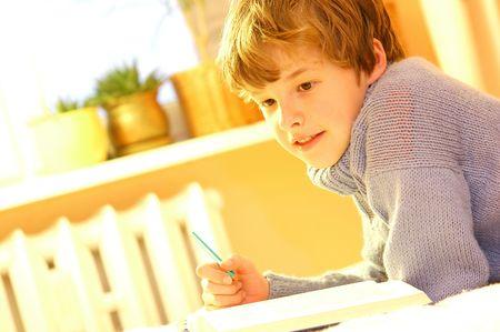 Boy doing homework on bed in sunny bedroom