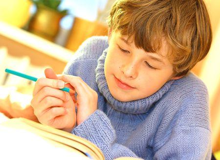 Boy doing homework on bed in sunny bedroom photo