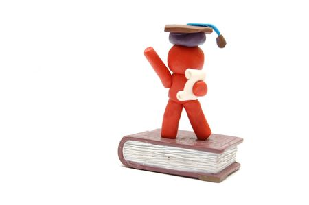 staying: Plasticine figure celebrating graduation with certificate and student hat staying on book