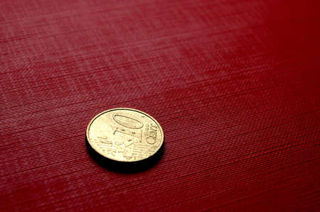 five cents: Gold coin (10 euro cent) on red surface