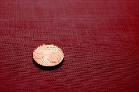 finanical: Coin (5 euro cent) on red surface Stock Photo