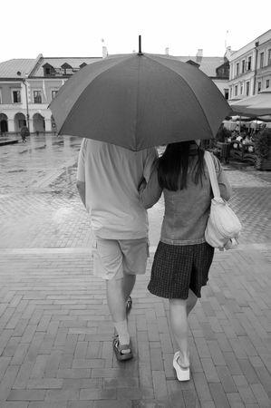 Couple with umbrella walking in rain  photo