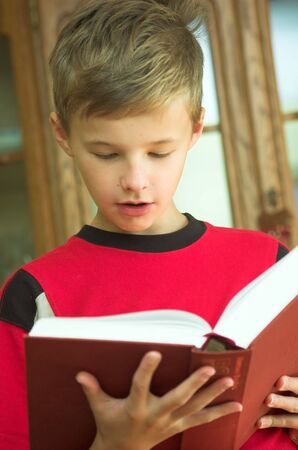 Young boy reading old, heavy book Stock Photo - 1134593