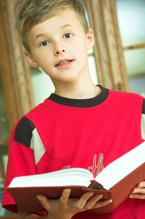Young boy reading old, heavy book photo
