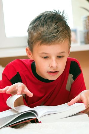 Young boy reading book on the bed  photo