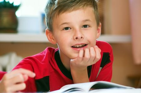 Portrait of young boy reading book on the bed photo