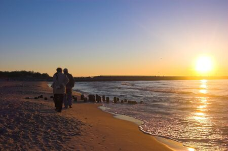 happiness people silhouette on the sunset: Couple walking on the beach at sunrise Stock Photo