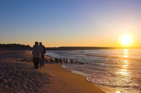 Couple walking on the beach at sunrise Stock Photo