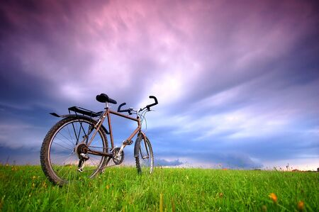 free background: Dynamic photo of bike standing alone in grassland - with free space above. Stock Photo