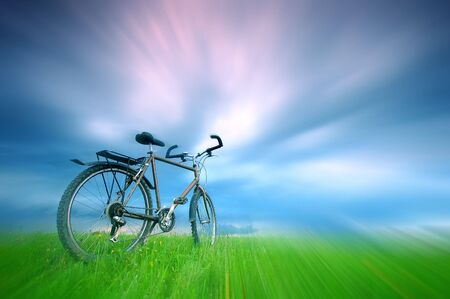 free space: Dynamic photo of bike standing alone in grassland - with free space above. Stock Photo