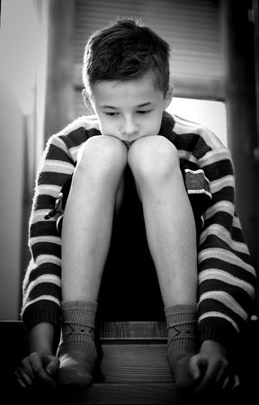 sadly: Portrait of young boy sitting sadly