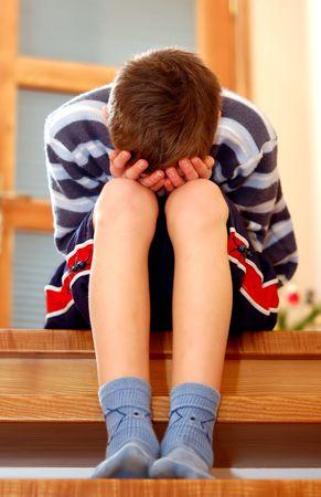 sadly: Ritratto di giovane ragazzo seduto tristemente