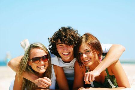 adolescentes riendo: Joven atractivo amigos que disfrutan juntos del verano playa