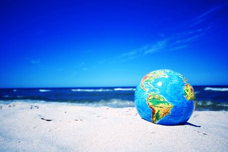 environmentalism: Earth globe on the beach. Ideal for Earth protection concepts, recycling, world issues, enviroment themes
