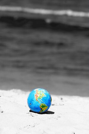 Earth globe on the beach. Ideal for Earth protection concepts, recycling, world issues, enviroment themes photo