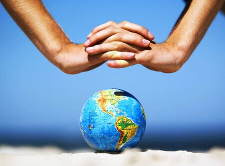 Earth globe on the beach and hands over it. Ideal for Earth protection concepts, recycling, world issues, enviroment themes photo