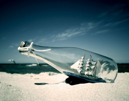 castaway: Bottle with ship inside lying on the beach. Conceptual image Stock Photo