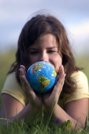 Pretty teen girl watching Earth globe. Conceptual image photo