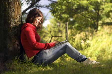 A beutiful student girl working on her laptop outdoor at sunny day Stock Photo - 3293025