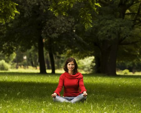 A beautiful young woman doing yoga in the park photo